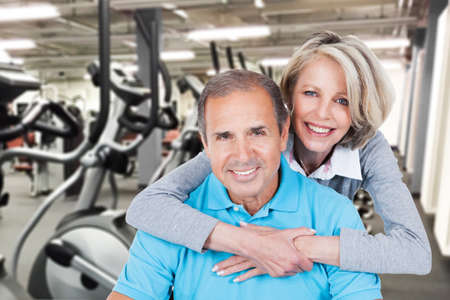 looking around: Portrait Of Happy Mature Couple Embracing At Gym