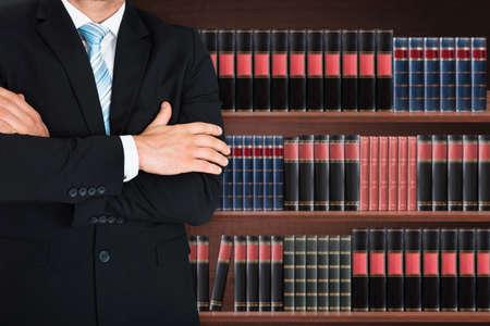 クローズ アップの腕を持つ男性の弁護士の交差の本棚の前に立っています。