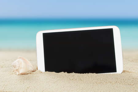 holiday destination: Closeup of tablet computer and shell on sand at beach Stock Photo