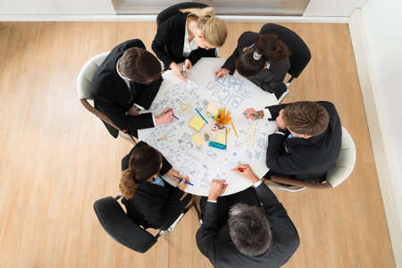 Group Of Businesspeople Discussing At Meeting In Office