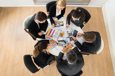 sales manager: Group Of Multiethnic Businesspeople With Color Samples In Office