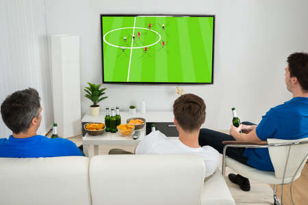 television: Three Men Sitting On Couch Watching Football Match On Television Stock Photo