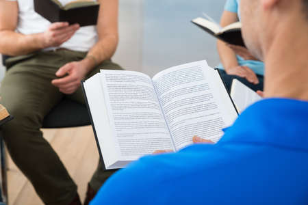 study group: Group Of Multiethnic Friends Reading Bible Together Stock Photo