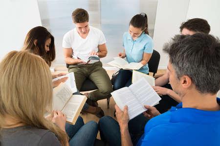 familia cristiana: Grupo de personas que se sientan junto lectura de libros