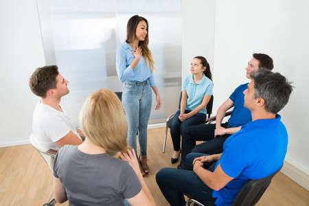 personas sentadas: Grupo de personas Mirando a la Mujer Explicando