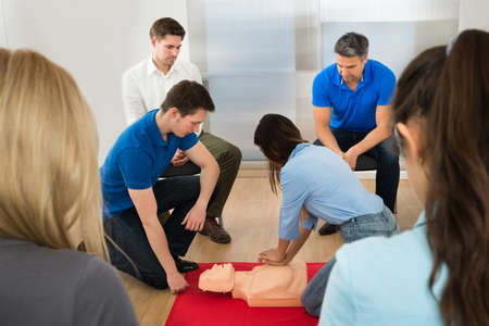 training group: Instructor Demonstrating Cpr Chest Compression On A Dummy