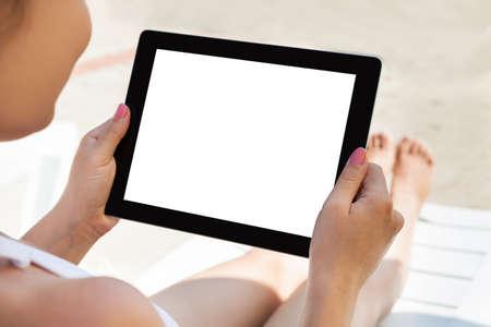 vysoký úhel pohledu: Mladá žena pomocí digitální tablety s prázdnou obrazovkou na resort Reklamní fotografie