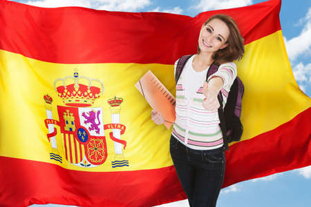 flag spain: Young Spanish Female Student Gesturing Thumb Up In Front Of Spain Flag