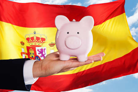 spain: Businessman Holding Piggybank In Front Of Spanish Flag Stock Photo