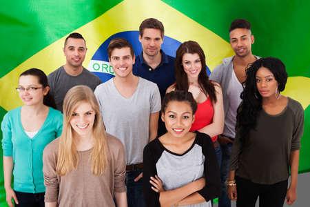 democracia: Feliz grupo multiétnico de personas se coloca delante de la bandera del Brasil