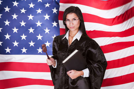 Female Judge With A Law Book And A Wooden Gavel Standing In Front Of American Flag photo