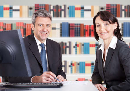advocate: Two Happy Mature Businesspeople Sitting At Office Desk