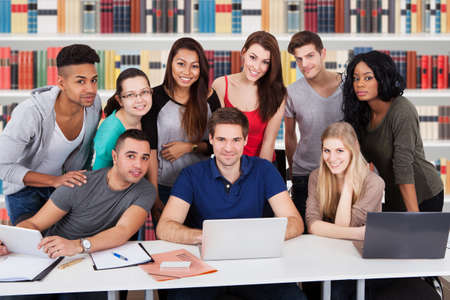 estudiando: Grupo de felices multiétnicos Amigos en la biblioteca estudiando