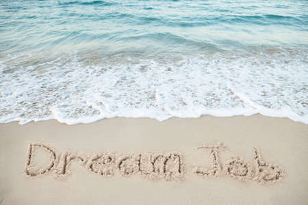 Dream Job written on sand by sea at beach Stock Photo