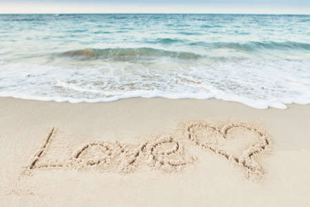 heart in sand: Love text and heart drawn on sand by sea at beach Stock Photo