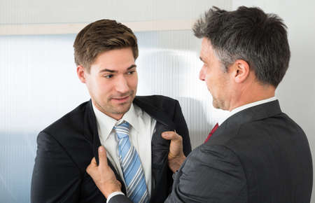 intimidation: Angry Mature Businessman Holding Coat Of Young Businessman