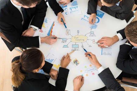 cloud shape: In Office Businesspeople Discussing About Cloud Computing Stock Photo