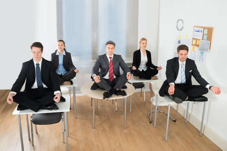 Meditating Businesspeople Sitting On Desk With Their Legs Crossed In Office Stock Photo