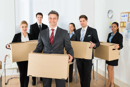 cardboards: Portrait Of Happy Multiethnic Employees In Office Holding Cardboard Boxes