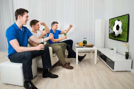 personas viendo television: Vista lateral de tres hombres que se sienta en el sofá que ve Partido de Fútbol en la televisión