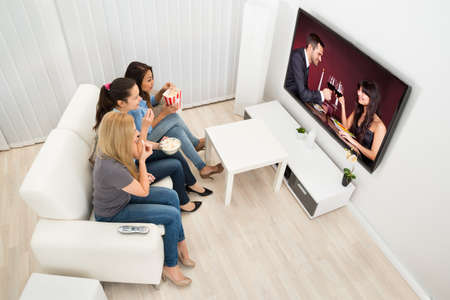 Multiethnic Young Women Sitting On Couch Watching Movie At Home photo