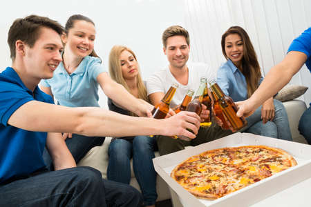 Group Of Multi-ethnic Friends Enjoying Pizza And Beer In Party photo