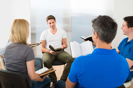 young woman reading bible: Man Explaining To His Friends From Scripture
