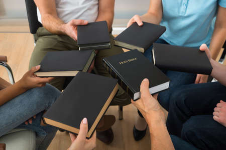 Close-up Of People Sitting Together Holding Holy Bible