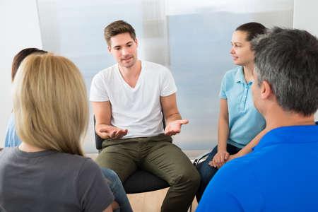 personas sentadas: La gente escuchando a un hombre gesticula con las manos