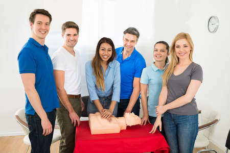 first class: Group Of Multiethnic People Learning How To Perform Cpr Stock Photo