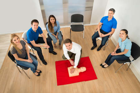 Verhoogde weergave van Eerste Hulp Instructeur Met Resuscitation Techniek Op Dummy