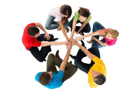apoyo social: Grupo de amigos que se sientan en un círculo de apilamiento manos sobre fondo blanco