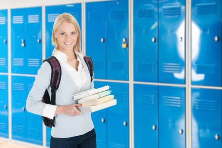 changing room: Young Female College Student With Stack Of Book In Changing Room Stock Photo