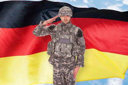 german soldier: Portrait Of German Soldier Saluting In Front Of Flag Stock Photo