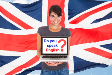 english text: Young Woman Holding Laptop Asking Do You Speak English In Front Of British Flag
