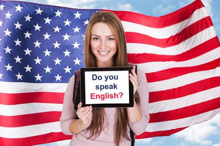 drapeau anglais: Jeune femme tablette numérique Tenir demandé Parlez-vous anglais Devant Drapeau Usa Banque d'images