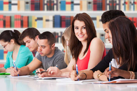 classmates: Portrait Of College Student Sitting With Classmates In Library
