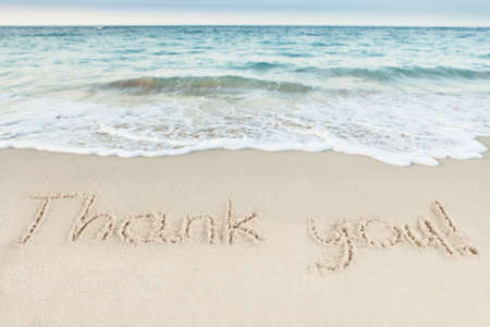 Thank you written on sand by sea at beach