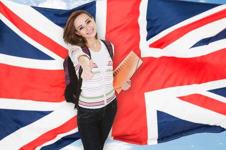 lekce: Mladý ženský student ukázal palec nahoru před britskou vlajkou