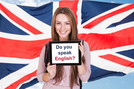 bandera inglesa: Mujer joven Holding Tableta digital Preguntar ¿Usted habla Inglés delante de la bandera británica