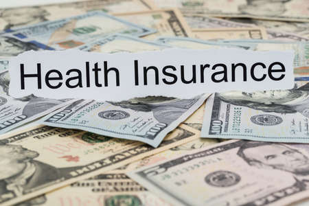Close-up Of Health Insurance Text On Piece Of Paper With Banknotes
