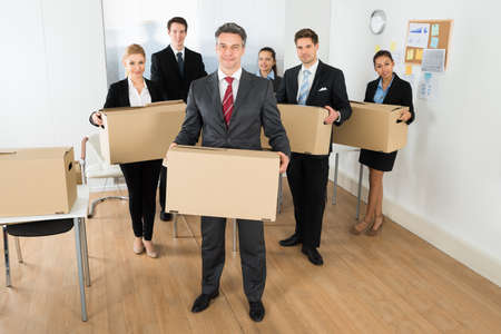 Portrait Of Happy Multiethnic Employees In Office Holding Cardboard Boxes photo