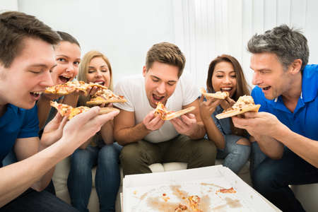 unhealthy eating: Group Of Multiethnic Friends Eating Pizza Together