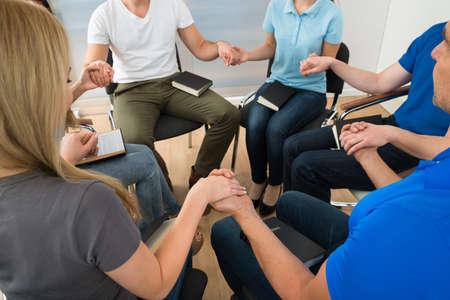 orando: Primer plano de personas que sostienen cada otros manos orando juntos