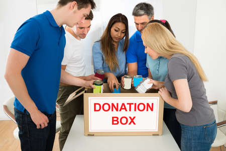 can food: Group Of Multiethnic People Holding Tin Can Looking Inside Donation Box Stock Photo
