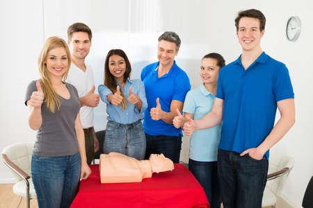 primeros auxilios: Grupo de personas multiétnicos que muestra el pulgar encima del gesto Mientras Aprendizaje Resucitación Formación