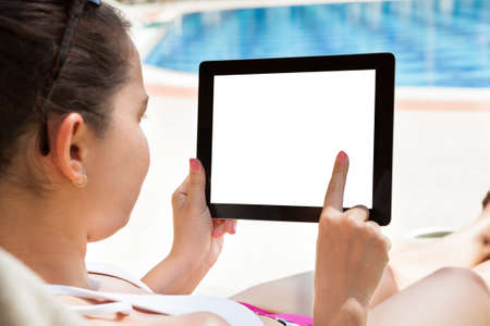 blank tablet: Young woman using digital tablet with blank screen at resort