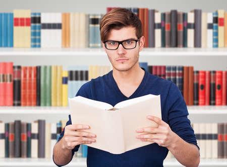 geek: Retrato de un Hombre que sostiene el libro en biblioteca