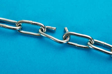 linked chain: Close-up Of Broken Silver Chain Over Blue Background