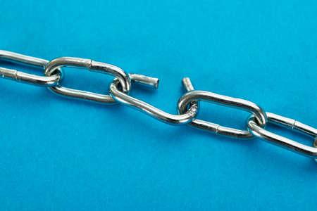 cadena rota: Primer plano de la cadena de plata rota sobre fondo azul Foto de archivo